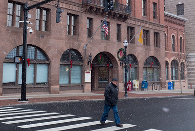 123016  Wesley Bunnell | Staff  Pedestrians cross in front of New Britain City Hall during Friday afternoons snow flurries.