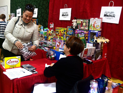 12/3/2016 Mike Orazzi | Staff Erica Gomez shops at the Amato's Toy and Hobby table during the New Britain YWCA's Winter Wonderland Weekend on Saturday. Helping her is Danica Levesque.