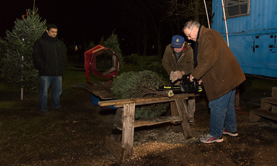 120516 Wesley Bunnell | Staff  Kiwanis Club members in Berlin are holding a Christmas Tree and wreath sale off of Massino Drive. Kiwanis member Morgan Seelye, middle, and Art Palmunen, shown right, prepare a tree to take home for Edward Arroyo of New Britain on the left.