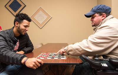 120516 Wesley Bunnell | Staff  OIC in conjunction with high school students got together on Monday afternoon at the Burritt School Apartments for a Christmas party with elderly residents of the building. High school senior Brandon Calez, shown left, plays checkers with resident Jesus Arroya .