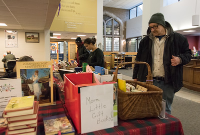 120616 Wesley Bunnell | Staff  Arthur Sutton of New Britain looks over the selection at the New Britain Library Christmas sale held on Tuesday afternoon. The sale featured new and gently used books and stocking stuffer gifts which were all donated to the library.
