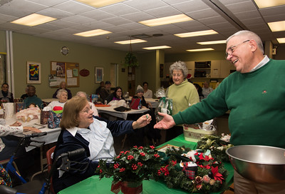 120916 Wesley Bunnell | Staff  The New Britain Senior Center held their holiday bazaar featuring hand made items for sale on Friday Dec 9.  Senior Center Director Mike Karwan, left, receives help from Chris Nicholaou in reading the winning ticket for the final raffle prize.