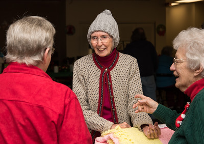 120916 Wesley Bunnell | Staff  The New Britain Senior Center held their holiday bazaar featuring hand made items for sale on Friday Dec 9.  Joy Rutty, center,  tries on a hand knitted winter hat while talking with Lillian Landrie, left, and Alice Gilbert.