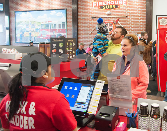 12/11/17 Wesley Bunnell | Staff Firehouse Subs opened for business on Monday at their new location at 594 Farmington Ave. Maria Hernandez, L, takes an order from Megan Huntley as she stands with her husband Chuck and son Chase, age 3.