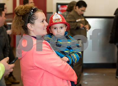 12/11/17  Wesley Bunnell | Staff  Firehouse Subs opened for business on Monday at their new location at 594 Farmington Ave. Megan Huntley holds her son Chase, age 3, while the look over the menu.