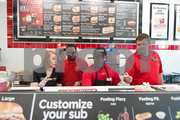 12/11/17 Wesley Bunnell | Staff Firehouse Subs opened for business on Monday at their new location at 594 Farmington Ave. Alayna O'Toole, L, works alongside Kesean Millard, 3rd from L, and Clint Wallburg.