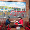 12/11/17  Wesley Bunnell | Staff<br /> <br /> Firehouse Subs opened for business on Monday at their new location at 594 Farmington Ave. Maria Hernandez takes a tray from a customer as he sits under a large mural of the Bristol Fire Department.
