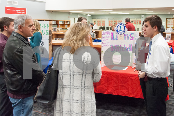 12/12/17 Wesley Bunnell | Staff The Berlin Upbeat Club held their 2017-18 Senior Expo on Tuesday evening at the high school. The expo featured Upbeat House Leaders discussing the focus of each house's activities. Gabriel Ramsey from Lions and Mitchell House, R, speaks with visitors.