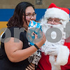 12/12/17  Wesley Bunnell | Staff<br /> <br /> New Britain OIC held their annual Christmas Party on Tuesday afternoon featuring food, music and presents for all members. Ashia Bravo, L, smiles as she receives a present from Executive Director of the New Britain Downtown District Gerry Amodio dressed as Santa.