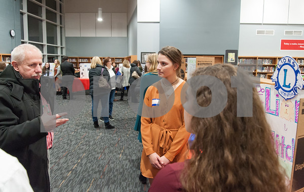 12/12/17 Wesley Bunnell | Staff The Berlin Upbeat Club held their 2017-18 Senior Expo on Tuesday evening at the high school. The expo featured Upbeat House Leaders discussing the focus of each house's activities. Natalie Couceiro from Lions and Mitchell House speaks with a visitor.