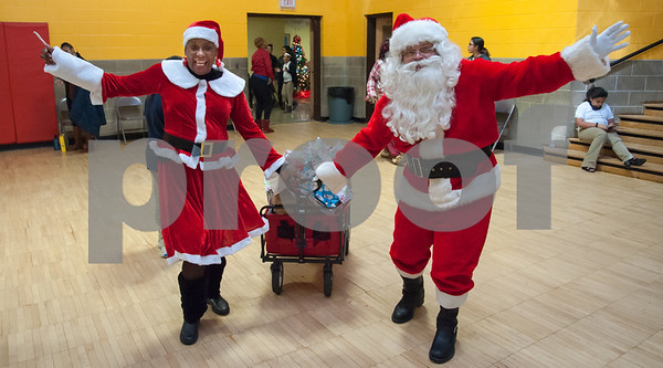 12/12/17 Wesley Bunnell | Staff New Britain OIC held their annual Christmas Party on Tuesday afternoon featuring food, music and presents for all members. OIC Executive Director Paulette Fox dressed as Mrs. Claus brings in a wagon full of presents along with Executive Director of the New Britain Downtown District Gerry Amodio dressed as Santa.