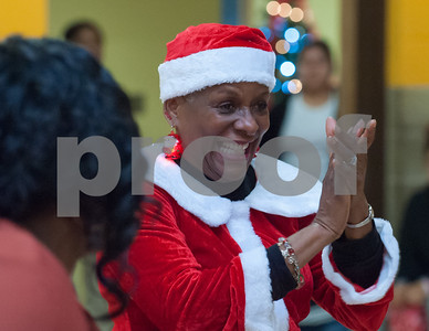 12/12/17  Wesley Bunnell | Staff  New Britain OIC held their annual Christmas Party on Tuesday afternoon featuring food, music and presents for all members. OIC Executive Director Paulette Fox smiles as children receive their gifts.