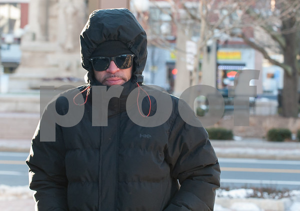 12/13/17 Wesley Bunnell | Staff Jason Figueroa is bundled up for the cold weather as he walks to his bus on Bank St. on Wednesday afternoon.