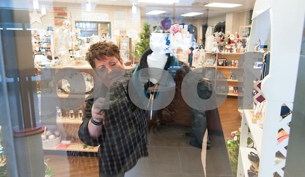 12/13/17 Wesley Bunnell | Staff The Hospital for Special Care held a ribbon cutting for their gift shop now run by Good Cause Gifts on Wednesday at noon. Store Manager Sharon Faucher makes changes to a store display as seen through the glass from the front lobby.