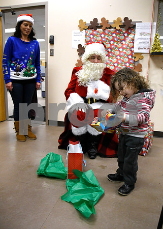 12/15/2017 Mike Orazzi | Staff Soliyi Green opens his gifts during a Christmas party Friday afternoon in Bristol at the Human Resources Agency of Bristol.
