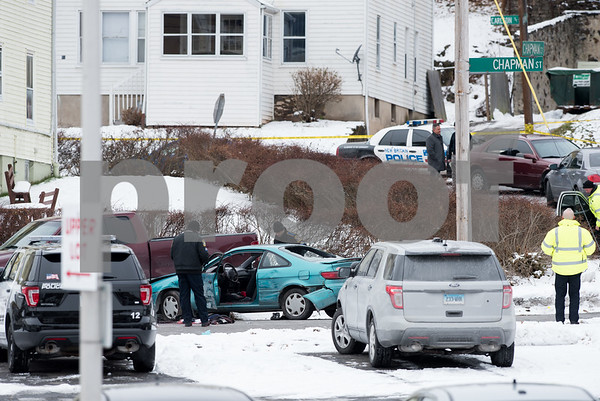 12/15/17 Wesley Bunnell | Staff State and New Britain Police on Friday morning at the intersection of Chapman St and Chapman Ct where an officer involved shooting occurred on Thursday evening involving three suspects in a green Toyota. State Police look over the vehicle.