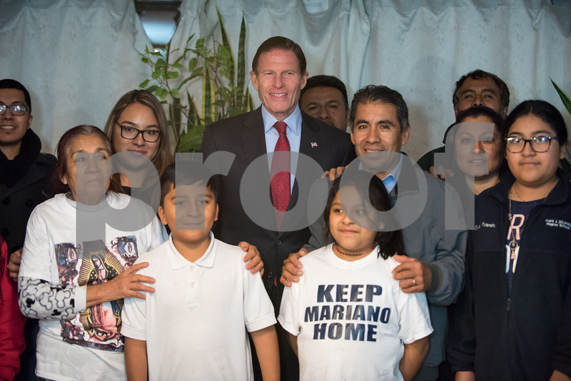 12/15/17  Wesley Bunnell   Staff<br /> <br /> New Britain resident Mario Cardoso Sr. was given a last minute stay of removal Friday afternoon on the day he was facing deportation to his native Mexico. Mario Cardoso Sr. poses to the right of Senator Richard Blumenthal during a family and friends photograph on Friday evening at the conclusion of a press conference held at their New Britain home.