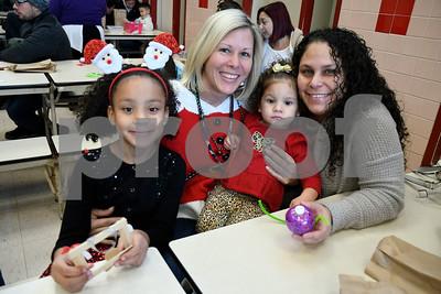 12/16/2017 Mike Orazzi | Staff Principal Karen Falvey Nylah Hardie,7, Elyse Perez,2, and Natasha Gerena at the Smith Elementary School's Breakfast with Santa on Saturday morning in New Britain.
