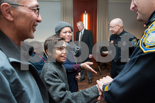 12/19/17 Wesley Bunnell | Staff 12 year old Armani Dante Rivera received recognition before the Police Commissioners meeting on Tuesday evening for his assistance to the New Britain Police Department. Armani shakes hands with Lt. Rodriguez as father Arquipo, L, and mom Victoria look on.