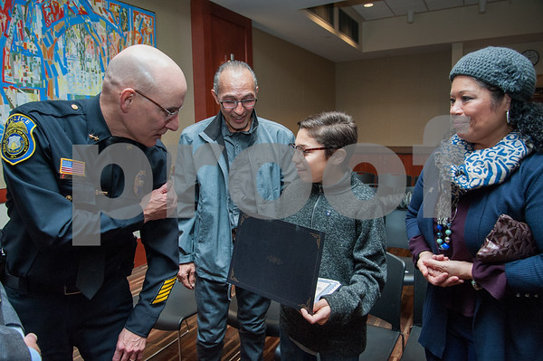 12/19/17 Wesley Bunnell | Staff 12 year old Armani Dante Rivera received recognition before the Police Commissioners meeting on Tuesday evening for his assistance to the New Britain Police Department. Police Chief James Wardwell points to his arm patch showing it is the same as presented to Armani Dante Rivera as father Arquipo, 2nd L, and mother Victoria look on.