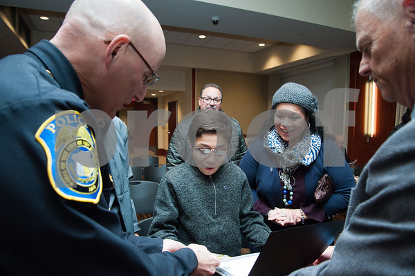 12/19/17 Wesley Bunnell   Staff 12 year old Armani Dante Rivera received recognition before the Police Commissioners meeting on Tuesday evening for his assistance to the New Britain Police Department. Armani Dante Rivera reacts after receiving an official New Britain Police patch from Chief James Wardwell, L, and commissioner chairman Howard Dyson, R, as his mother Victoria Rivera looks on.