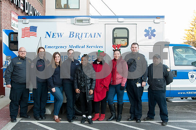 12/21/17  Wesley Bunnell | Staff  New Britain Emergency Services Stuff A Truck matches families with children who are part of The Friendship Center's housing and sheltering programs with donated gifts from other agencies, local retailers and staff. This year's program was partnered with the Hospital of Central Connecticut and the New Britain Fire Department. Posing for a photo just prior to delivering the items are New Britain EMS Captain Patrick Ciardullo, New Britain Fire Department's Petra Chesanek, New Britain EMS' Lillian Gopoian, New Britain EMS' Kristen Farrell, Niyanna Allen,  The Friendship Center's Tammy Roman and Ingrid Zhan, New Britain EMS's Matthew May and New Britain Fire Department's Marco Costa.