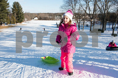 12/26/17  Wesley Bunnell | Staff  Families took advantage of good sledding conditions at Page Park on Tuesday afternoon. Corinne Setula, age 9, carries her sled back uphill after a run.
