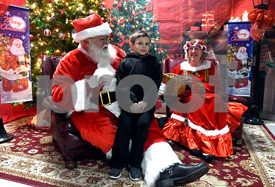 12/8/2017 Mike Orazzi   Staff Seven-year-old Noah Olson meets with Santa and Mrs Claus during the annual tree lighting held at the Plainville Fire Department Friday evening.
