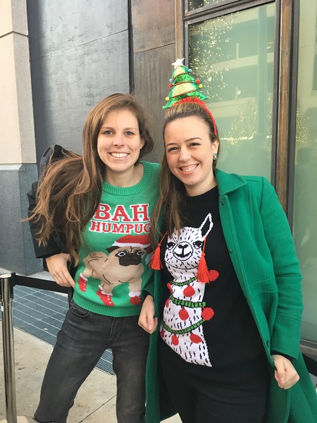 Two girls wear animal themed holiday sweaters