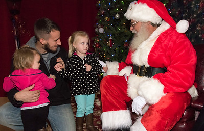 12/06/18  Wesley Bunnell | Staff  Plainville held a tree lighting ceremony on Thursday at Fire HQ featuring singing, refreshments and a visit from Santa with a chance to sit on his lap. Garrett Quealy brings his two daughters DaKota, age 2, and MaKenna, age 4, to talk with Santa.