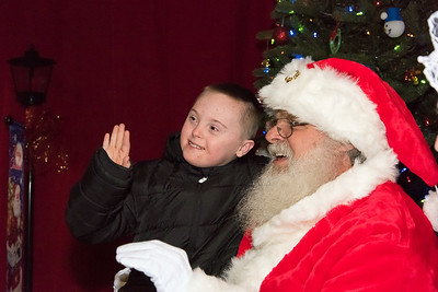 12/06/18  Wesley Bunnell | Staff  Plainville held a tree lighting ceremony on Thursday at Fire HQ featuring singing, refreshments and a visit from Santa with a chance to sit on his lap. Jacob LeGeyt, age 10, waves back to his family while sitting on Santa's lap.