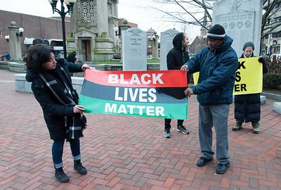 12/14/18  Wesley Bunnell | Staff  Activists and family members spoke on Friday afternoon at Central Park, across from city hall, in remembrance of the police involved shooting on Chapman St one year ago. Activist Cornell Lewis, R, helps unfold a Black Lives Matter banner.