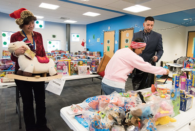 12/17/18  Wesley Bunnell | Staff  Glenda Negron picks out toys for ages two, three and twelve year old children at the New Britain Housing Authority's 9th annual toy donation on Monday afternoon with the help of Self Sufficiency Coordinator Nancy Copeland, L, and Senior Family Self Sufficiency Coordinator Eric Montanile, R.