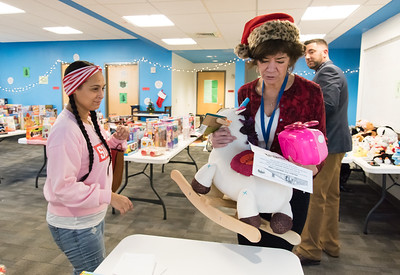 12/17/18  Wesley Bunnell | Staff  Glenda Negron picks out toys for ages two, three and twelve year old children at the New Britain Housing Authority's 9th annual toy donation on Monday afternoon with the help of Self Sufficiency Coordinator Nancy Copeland and Senior Family Self Sufficiency Coordinator Eric Montanile.