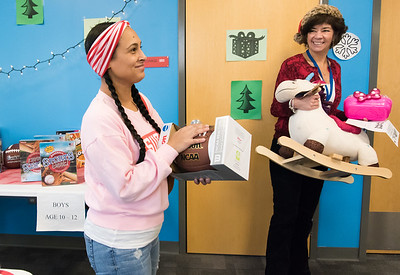 12/17/18  Wesley Bunnell | Staff  Glenda Negron picks out toys for ages two, three and twelve year old children at the New Britain Housing Authority's 9th annual toy donation on Monday afternoon with the help of Self Sufficiency Coordinator Nancy Copeland.