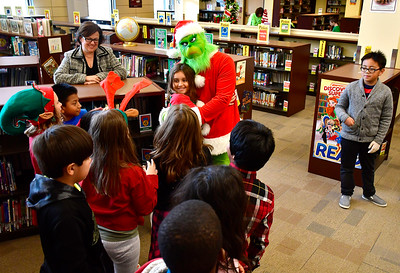 12/20/2018 Mike Orazzi | Staff The Grinch greets Mackenzie Ciechoski  at the West Bristol School during their Grinchmas, a month-long celebration of literacy events and community services on Thursday afternoon.