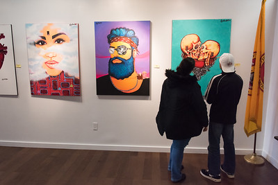 12/26/18  Wesley Bunnell | Staff  Tilly Ferreira, L, and Joe Cameron look over the artwork of Olivia Be Nguyen who goes by the artist name of Flyabomb at Gallery 66 on Wednesday afternoon. The artist is holding a meet and greet on January 12th at Gallery 66 from 7pm until Midnight.