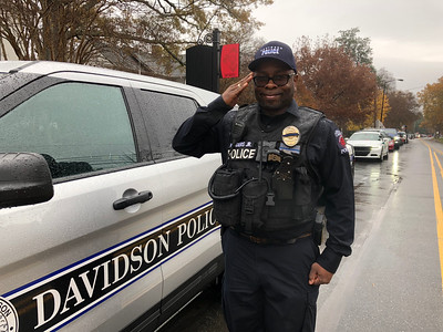 Davidson police detective Vernon Siders renders a hand salute as the parade gets ready to begin. This former Marine won't wilt in the rain.
