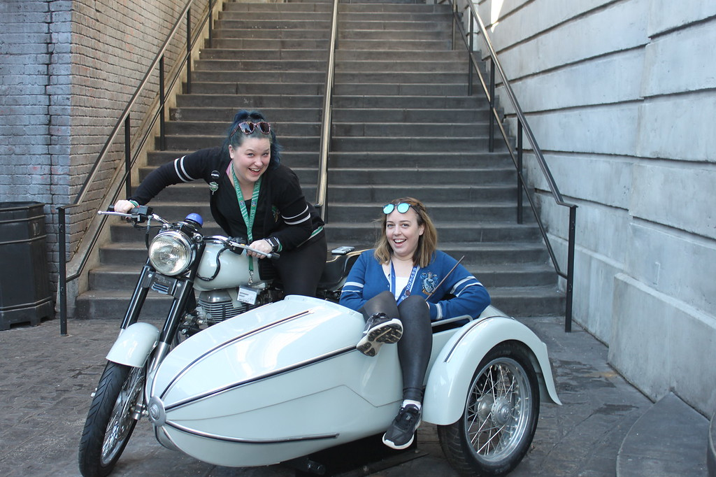 Two girls sit in a non functional motorbike in Diagon Alley at Universal Orlando Resort