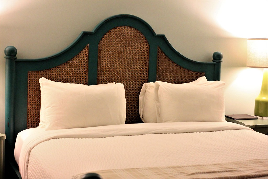 Bed at Hotel Simone with teal frame and caning