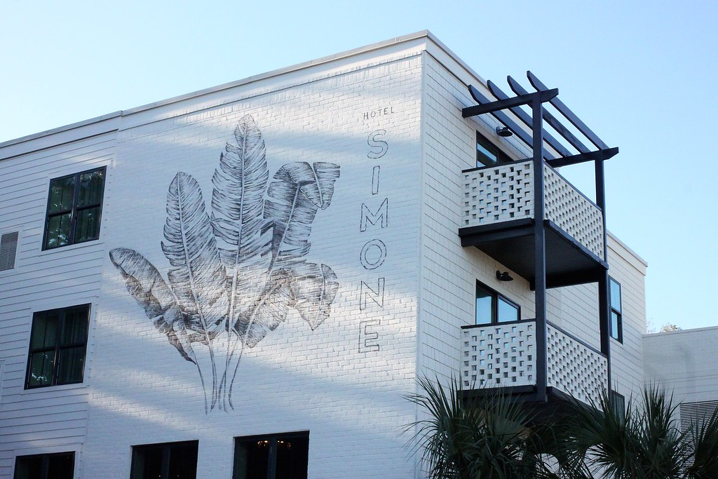 Hotel Simone exterior with white brick and painting of a palm frond