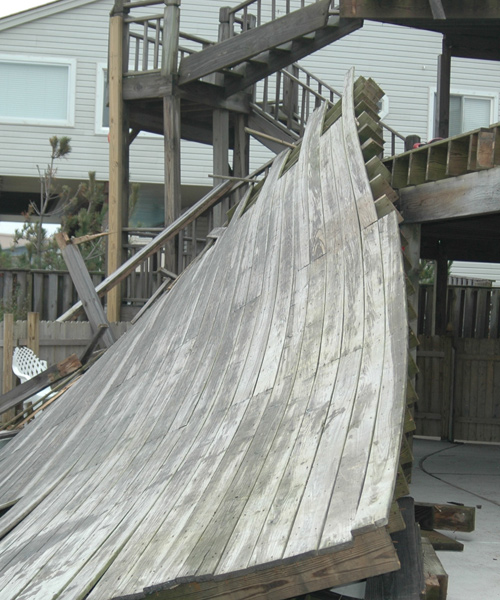 View from ground N end, up toward stairs. Note added support, (new-lumber) nailed to stairway support.<br /> Also here you can visualize how some injured, slid down the deck surface to the pool and or concrete surface below the deck.