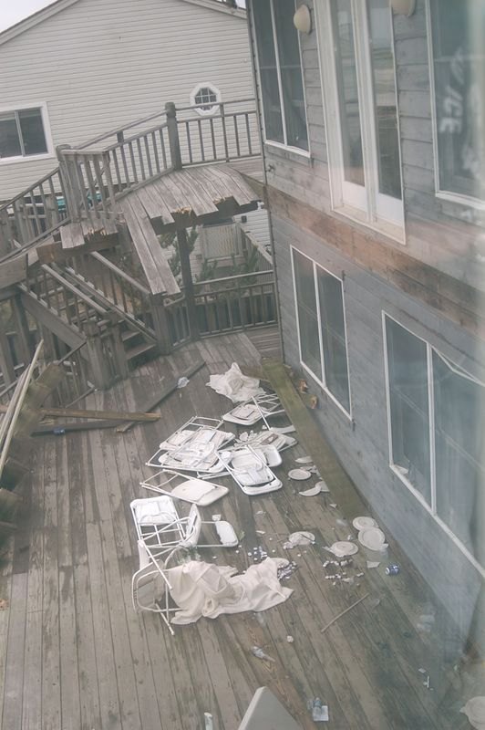 View through third floor window, to remaining portion of second level deck, with debris.