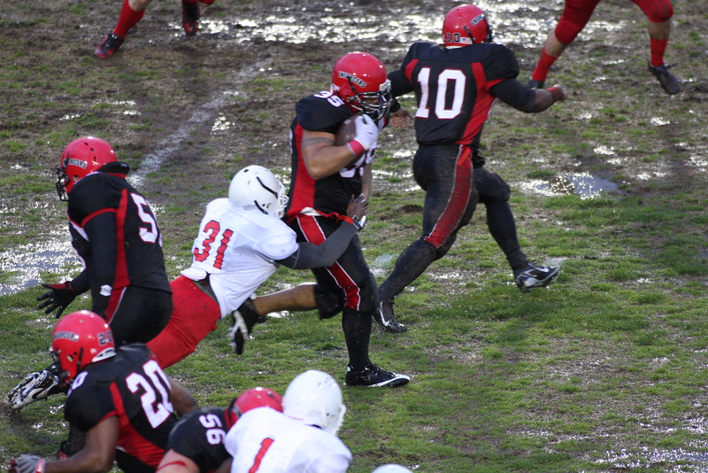 #35 Wilson Ueligitone RB runs while #31  attempts the tackle.