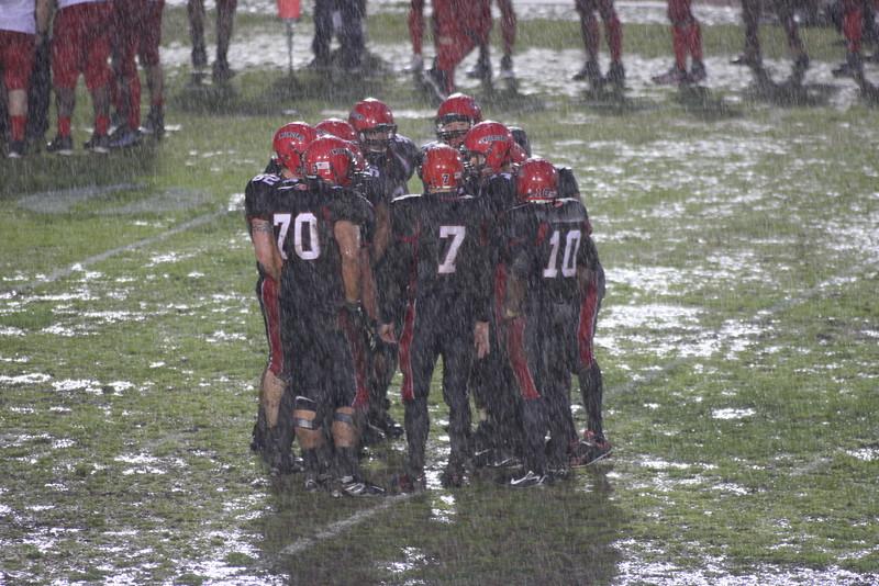 The Enforcers huddle during a downpour.