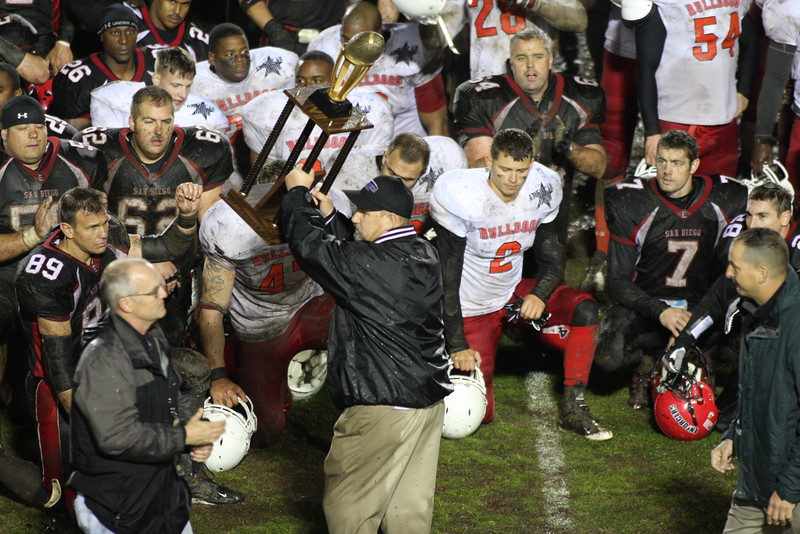 Enforcer Head Coach Brian Salmon raises the Defender Bowl Trophy in victory.