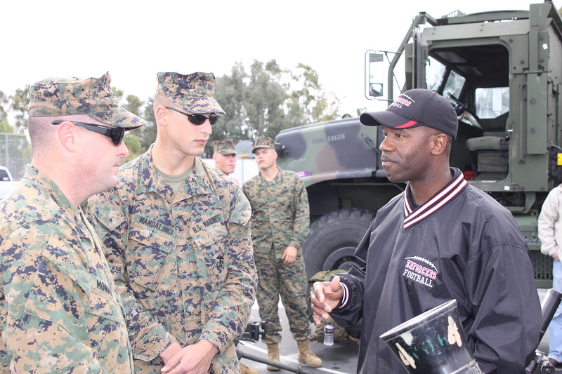 Defensive Backs Coach Eddie Brock chats with some Marines.