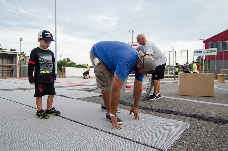 Dominic DeVito, 5, looks on as dad Anthony works to install a new floor at the Fitchburg Street Hockey League rinks at Coolidge Park in Fitchburg. This is the culmination of a years-long effort to update the rinks, using parts of the old Landry Arena along the way. SENTINEL & ENTERPRISE / Ashley Green