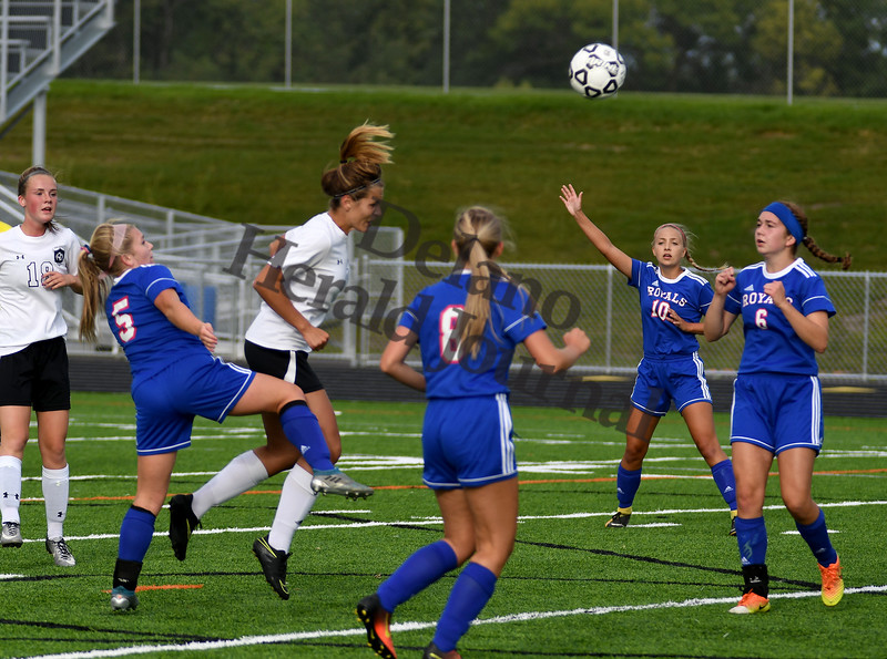 Delano senior Aubri Farniok plays a header through a line of Watertown-Mayer defenders and towards the goal Tuesday night in Delano.