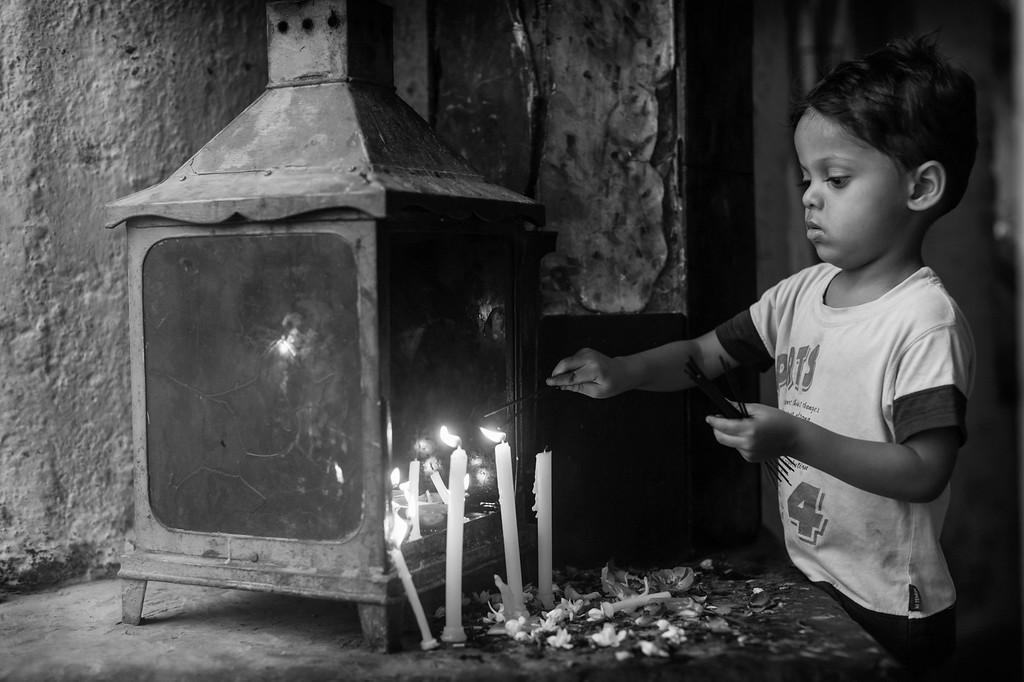 Boy lights candles, Dargah of Qutb Sahib, Mehrauli